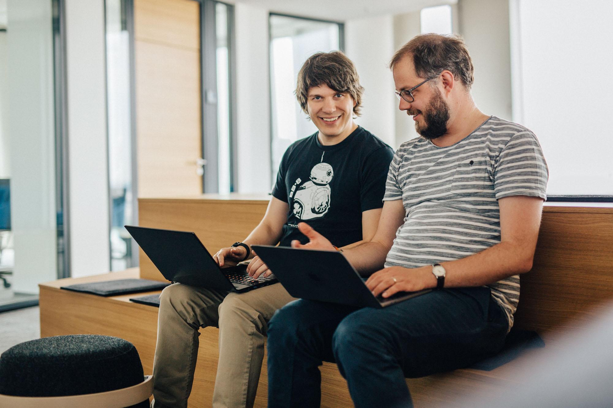 Kollegen vor MacBooks arbeiten zusammen min den Tanzenden Türmen
